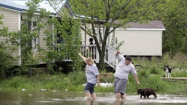 Eve Andrews, left, and her son Brandon Andrews walk through floodwater to get back to their home in Poplar Bluff, Mo., on Monday.
