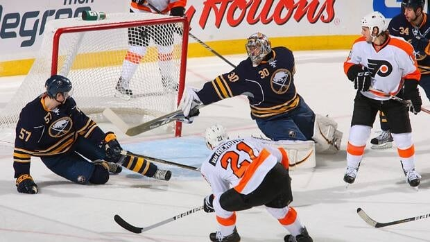 Tyler Myers, left, and goalie Ryan Miller of the Buffalo Sabres deflect a shot by James van Riemsdyk, foreground, of the Philadelphia Flyers.