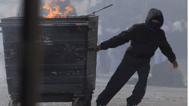 A masked youth pulls a burning garbage bin set on fire by rioters in Hackney, east London, on Aug. 8, part of the rioting that consumed Britain for several days.