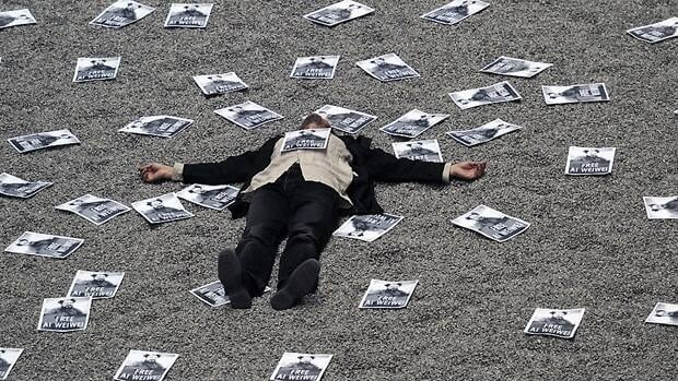 A protester rests on the Sunflower Seeds installation by Ai Weiwei at London's Tate Modern on Saturday, after scattering hundreds of posters calling for the Chinese artist's release.
