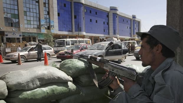 An Afghan policeman watches a Kabul street from his post across from one of the city's more modern buildings on April 26, 2011. The southern Afghan city has been experiencing a construction boom recently but still remains unsafe despite several years of foreign military intervention.