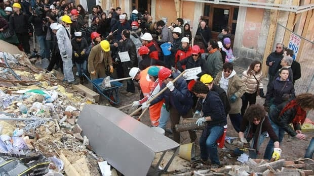 Residents of L'Aquila, Italy clean up rubble the April 6, 2009 earthquake. On Thursday, Italy charged seven scientists for failing to warn residents of the quake.