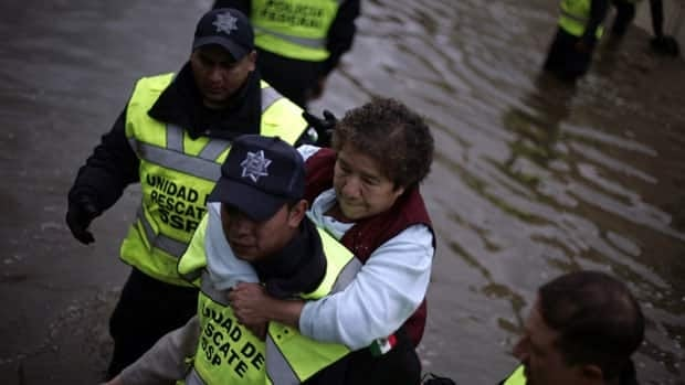 A woman is carried out of her flooded home in a neighbourhood in Mexico City on Saturday after torrential rains hit large parts of central Mexico.