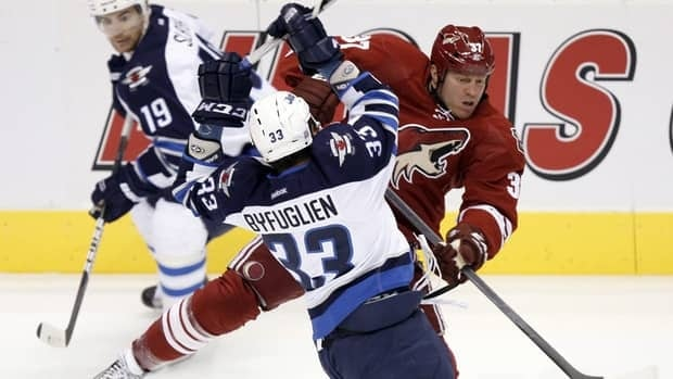 Winnipeg Jets defenceman Dustin Byfuglien, front, checks Phoenix Coyotes left winger Raffi Torres in October. The Jets and Coyotes will face off Monday night in Winnipeg.