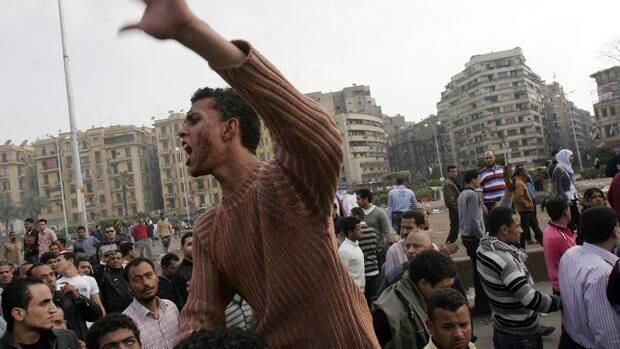 A protester chants slogans while riding on another man's shoulders following an attack by security forces in Tahrir Square, in Cairo on Saturday, April 9, 2011. Soldiers beat hundreds of protesters  in the latest sign of tensions between Egypt's ruling military and the country's protest movement.
