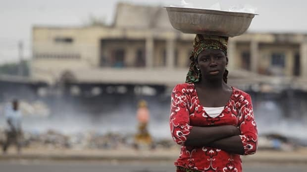 A girl stands near burning trash in the Abobo neighborhood of Abidjan, Ivory Coast, on Friday, a day after soldiers killed at least six female protestors in Abobo (Rebecca Blackwell/Associated Press)