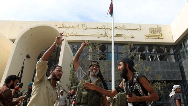 Libyan National Transitional Council fighters celebrate after seizing control of the Ouagadougou conference centre in Sirte on Sunday.