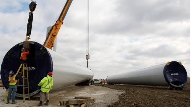 Workers accept delivery of wind turbine towers at the Pointe-Aux-Roches Wind Project in Essex County, Ont. on Nov. 26, 2010. Industry experts say the size of the future renewable job market is uncertain but many companies say they expect a shortage of skilled labour.