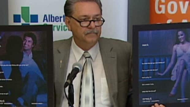 Alberta Health Minister Gene Zwozdesky displays posters which will be used in a campaign targeting high rates of STDs in the province.
