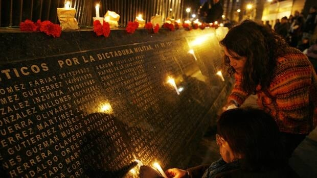 """Relatives of people who went missing during Augusto Pinochet's regime, look at names on the monument to those detained and disappeared in the city of Valparaiso, northwest of Santiago. The monument reads """"Executed political."""""""