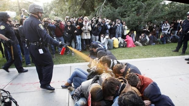 A University of California police officer uses pepper spray to move Occupy UC Davis protesters on Nov. 18. Chancellor Linda Katehi has set a 30-day deadline for an investigation into the incident.