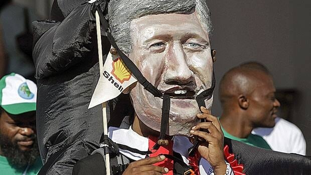An activist wears a mask depicting the face of Prime Minister Stephen Harper during a protest at climate change talks in Durban, South Africa, Dec. 5.