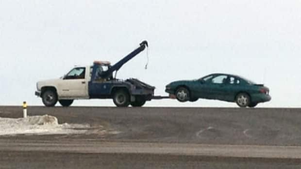 A vehicle that is part of an RCMP investigation into the shooting deaths near Claresholm, Alta., is towed away from the scene.