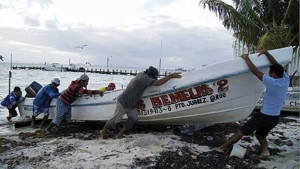 Fishermen secure their boat on October 25 in anticipation of Hurricane Rina's arrival in Cancun, Mexico.