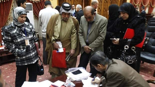 Families members of the victims of a September 2007 shooting by Blackwater security guards sign power of attorney documents to the Iraqi government in Baghdad, Jan. 18. 2010. Iraq's government was collecting signatures for a class-action lawsuit from those who were wounded or lost family in incidents involving the U.S. private security firm formerly known as Blackwater.