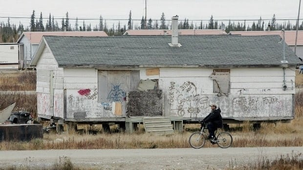 A native boy rides his bike past one of the many run down homes on the Kashechewan native reserve in northern Ontario in this file photo.