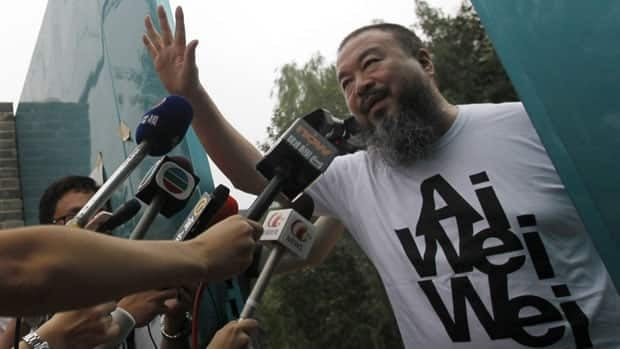 Activist artist Ai Weiwei opens the gate to talk to journalists gathered outside his home in Beijing on Thursday. He refused to talk about his detention.