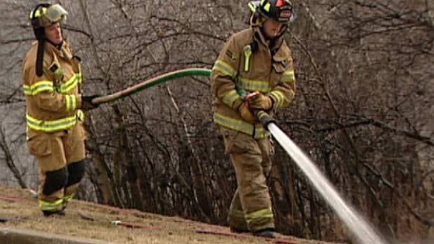 Firefighters water down hot spots along the top of Kennendale Ravine in Clareview Monday evening.