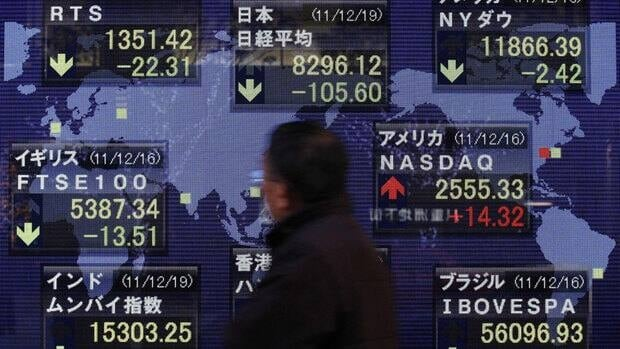 A man walks past an electronic stock board in Tokyo showing drops on most world markets Monday following the death of North Korean ruler Kim Jong-il.