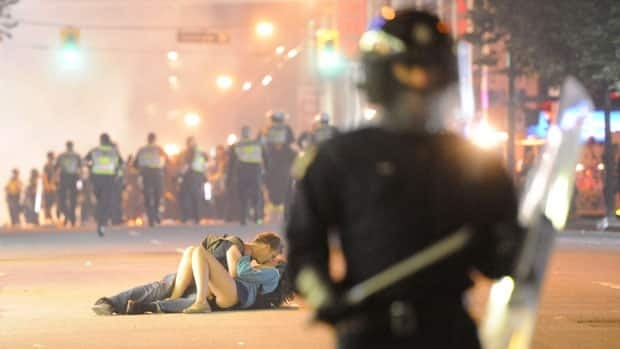 The so-called kissing couple is shown embracing on a Vancouver street as riot police battled overzealous Canucks fans following their Stanley Cup loss.