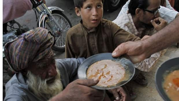 Poor people get free food distributed by a non-governmental organization in Karachi, Pakistan, on Monday. An Oxfam International report released Tuesday says the food crisis will worsen if governments and big companies don't take action.