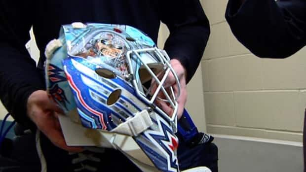 Goalie Chris Mason shows off his Winnipeg Jets mask after a practice at the MTS Ice-Plex Monday.