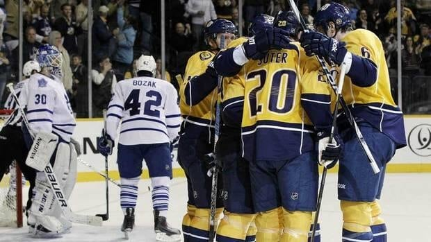 Nashville Predators defenceman Ryan Suter, front centre, celebrates with teammates after potting a goal against Ben Scrivens, left, and the Toronto Maple Leafs on Thursday night.