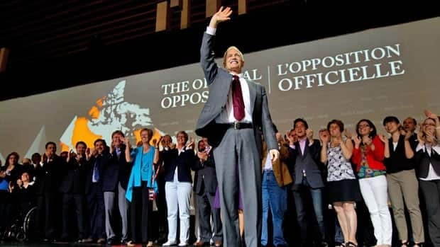 NDP leader Jack Layton is flanked by his fellow MPs as he waves before delivering a speech to open the party's 50th anniversary convention in Vancouver, B.C., on Friday June 17, 2011.