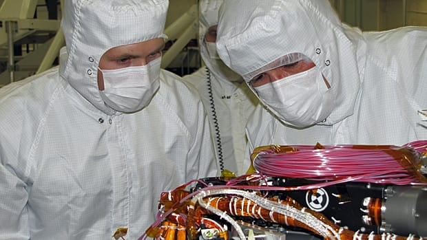 Grad student Nicholas Boyd, left, and principal investigator Ralf Gellert, both of the University of Guelph, prepare for the installation of the alpha particle X-ray spectrometer sensor head during testing at NASA's Jet Propulsion Laboratory in Pasadena, Calif.