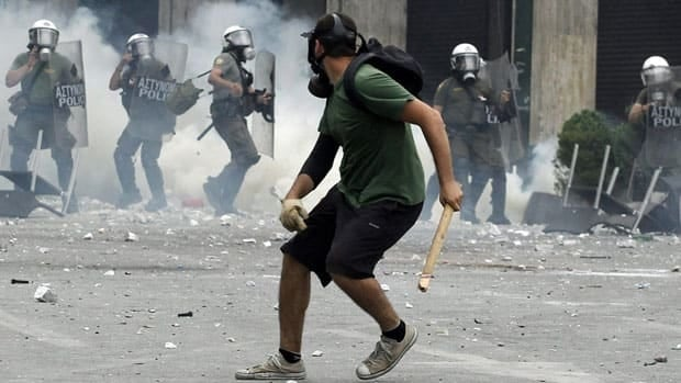 A protester throws a stone towards policemen during clashes at Athens' main Syntagma square, in central Athens, on Wednesday, June 29, when anti-austerity rioting reached its peak.