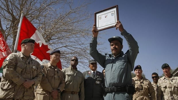 An Afghan police officer holds his certification during a graduation ceremony at the Provincial Reconstruction Team compound run by Canadian soldiers in Kandahar, in February 2010.