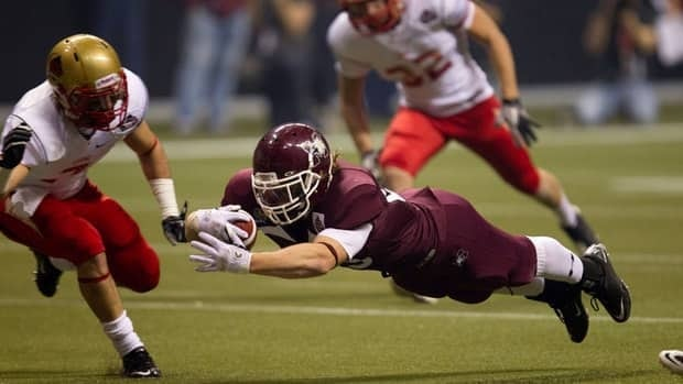 McMaster University Marauders' Christopher Pezzetta scores a touchdown as Laval University Rouge et Or's Adam Thibault and Jonathan Laliberte look on during the first half of the Vanier Cup on Friday.