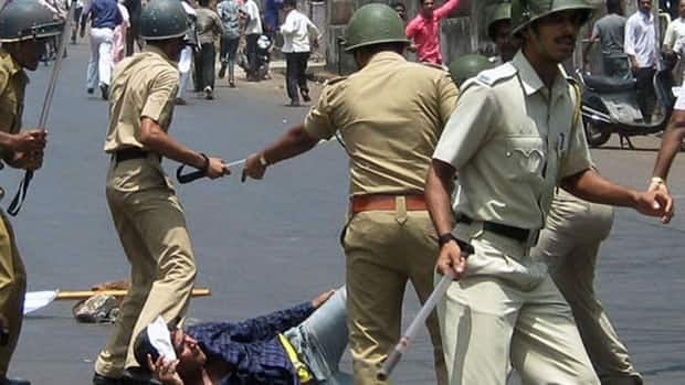 Police officers beat a man during a protest in Ratnagiri, south of Mumbai, on Tuesday. Indians protesting against a planned nuclear power plant attacked a hospital and torched buses.