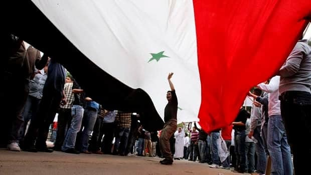 Syrian protesters hold a giant national flag as others shout slogans against the country's president during a demonstration in front of the Syrian Embassy in Nicosia, Cyprus, on Friday.