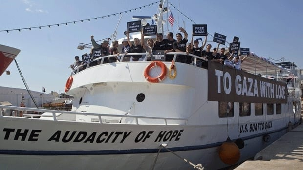 Activists from the U.S. stand on their boat, named the Audacity of Hope, which briefly made it out to sea on Friday night before being intercepted by the Greek coast guard.