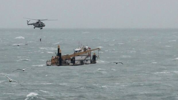 A helicopter flies over a rig while searching for 10 oil industry contractors who remain missing after they had evacuated the rig during tropical storm Nate in the Bay of Campeche on Saturday.