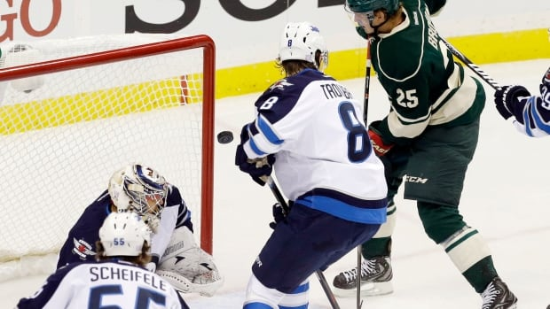 The puck glances off the glove of the Minnesota Wild's Jonas Brodin as he scores against Winnipeg Jets goalie Ondrej Pavelec in the first period Thursday in St. Paul, Minn.