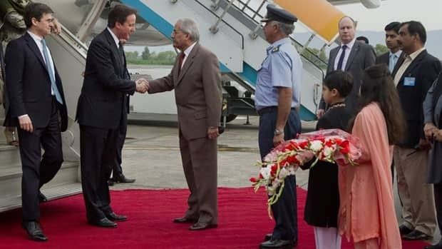 British Prime Minister David Cameron, second from left, is greeted by Minister of Inter-Provincial Co-Ordination Raza Rabbani after arriving at Rawalpindi. Cameron arrived in Pakistan on Tuesday for meetings with government and opposition leaders.