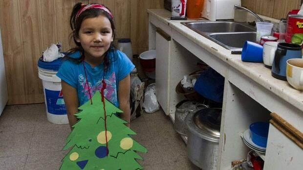 Five-year-old Verna Iahtal shows off her home-made Christmas tree in her home in Attawapiskat, Ont. Twenty-one people live in the condemned house that has plastic on the ceilings to stop water entry.