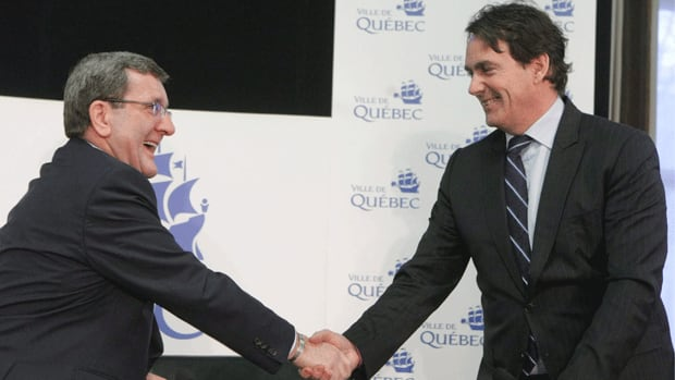 Quebec city mayor Regis Labeaume, left, and Pierre-Karl Peladeau, CEO of Quebecor, shake hands in March after the two came to terms on a deal involving the city's new arena.