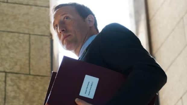 Defence Minister Peter MacKay makes his way from the foyer of the House of Commons following question period last June. A Liberal MP is questioning the criteria behind a decision to close some government service centres that process EI claims. The centres in MacKay's riding and another Tory-held Nova Scotia riding will not close.