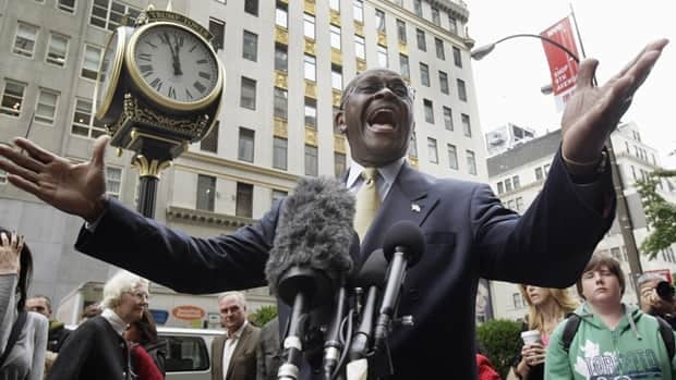 In this Oct. 3, 2011 file photo Republican presidential candidate Herman Cain stops to address the media as he arrives for a meeting with developer Donald Trump, in New York. Cain is reassessing his presidential bid, according to an adviser.