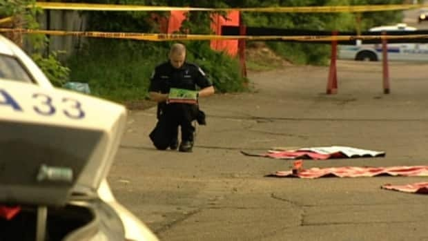An Edmonton police officer investigates the scene northwest of downtown where a man was killed Friday.