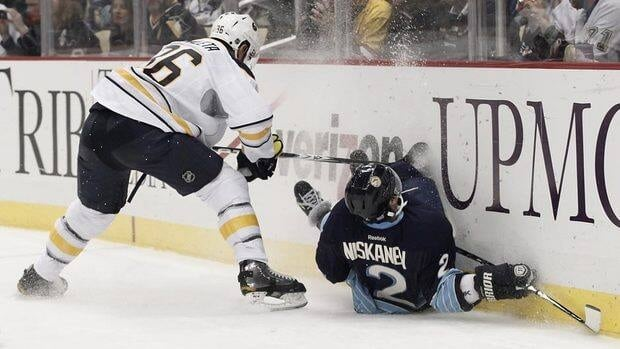 Pittsburgh's Matt Niskanen, right, slides into the boards in front of Buffalo's Patrick Kaleta.