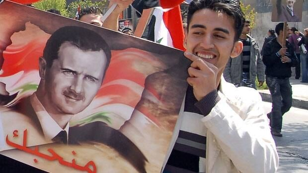 A pro-Syrian President Bashar Assad supporter in Damascus, Syria, where on Tuesday Assad's cabinet resigned.