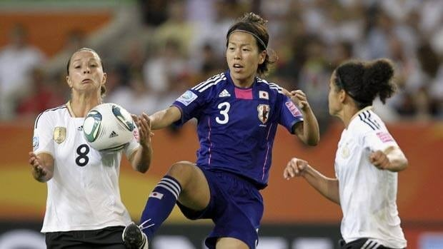 Japan's Azusa Iwashimizu, middle, kicks the ball between Germany's Inka Grings and Celia Okoyino Da during Saturday's match.