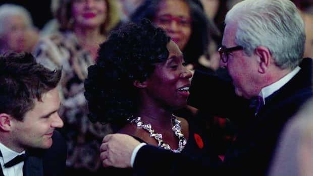 Esi  Edugyan, centre, is congratulated by her publisher Patrick Crean, right, while husband Steven Price looks on as she makes her way to the podium to accept the Scotiabank Giller Prize award for the book  Half-Blood Blues.