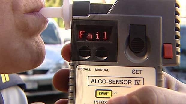 Police take a breathalyzer sample from a driver.
