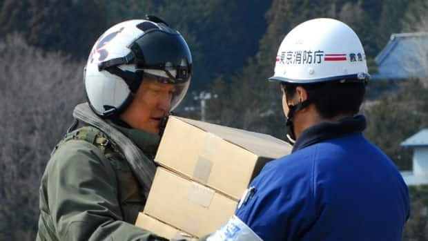 An American navy officer hands supplies to a Japanese aid worker during relief efforts near Sendai, Japan. Canada is offering to send military and other aid as well.