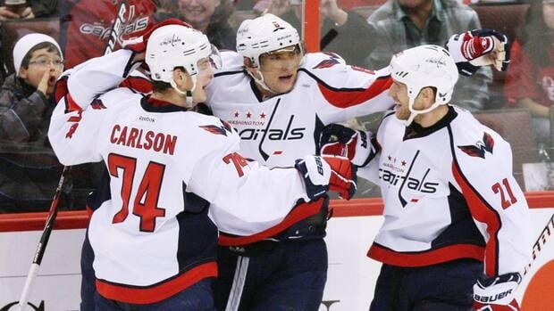 Washington Capitals Alex Ovechkin(8) celebrates his third period goal with teammates Brooks Laich (21) and John Carlson (74) in Ottawa on Wednesday. The Capitals beat the Ottawa Senators 5-3.